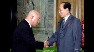 Isao Iijima, de Japanse adviseur van premier Abe, schudt handen met Kim Yong-nam, het ceremoniële staatshoofd van Noord-Korea